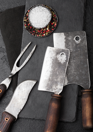 Vintage meat knife and fork and hatchets with stone chopping board and black table background. Butcher utensils.