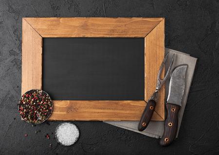 Wooden menu board and vintage meat knife and fork on kitchen towel and black stone table background. Butcher utensils.  Banco de Imagens