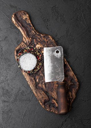 Vintage meat knife hatchet on vintage chopping board and black stone table background. Butcher utensils.