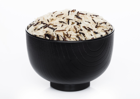 Black bowl of raw organic basmati long grain and wild rice on white background.  Banque d'images
