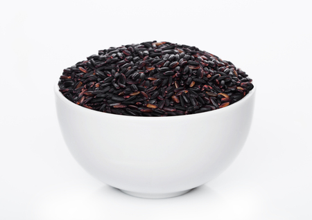 White bowl of raw organic black venus rice on white background.