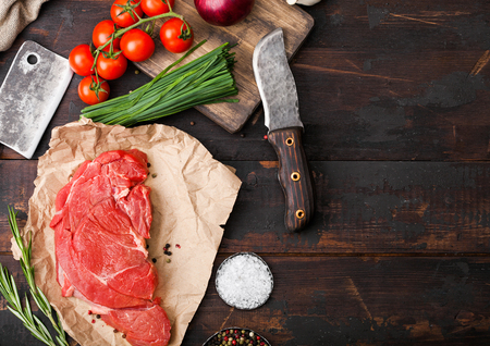 Fresh raw organic slice of braising steak fillet on butchers paper with fork and knife on dark wooden background. Red onion, tomatoes with salt and pepper and herbs. Standard-Bild - 122746711