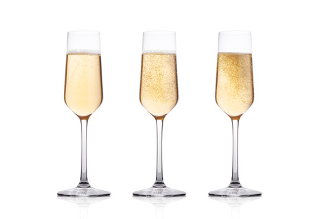 Elegant glasses of yellow champagne with bubbles on white background with reflection