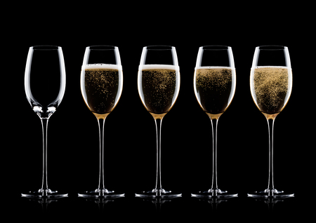 Elegant glasses of yellow champagne with bubbles on black background with reflection 스톡 콘텐츠