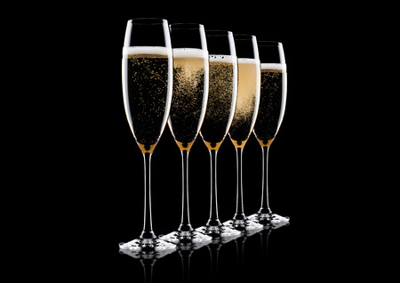 Elegant glasses of yellow champagne with bubbles on black background with reflection Imagens