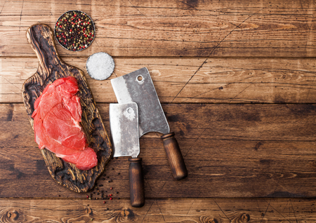 Fresh raw organic slice of braising steak fillet on chopping board with meat hatchets on wooden background.