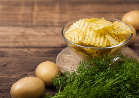 Homemade potato crisp chips inside glass bowl with fresh raw dill on wood background and raw potatoes.
