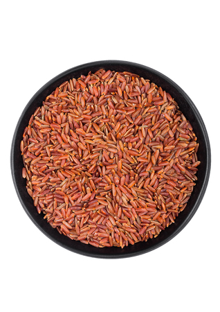 Black bowl of raw organic red rice on white background. Top view