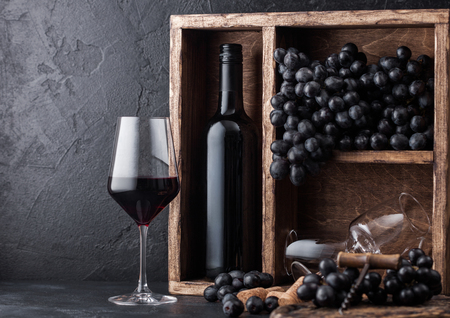 Luxury bottle of red wine with dark grapes inside vintage wooden box on black stone background. Elegant wine glass with corks and corkscrew on black board.