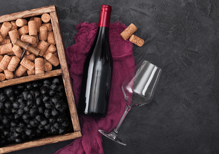 Bottle of red wine on red cloth with empty glass and dark grapes with corks and corkscrew inside vintage wooden box on dark wooden background. Stock Photo