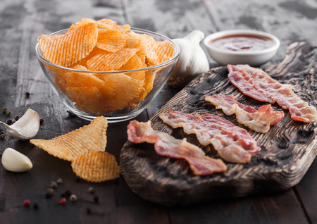 Potato crisps with backon flavour with grilled bacon rashers on vintage chopping board with garlic and sauce on wood background.