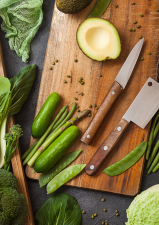Assorted green toned raw organic vegetables in wooden box on dark stone background. Avocado, cabbage, cauliflower and cucumber with trimmed beans and chopping board with knife. Imagens
