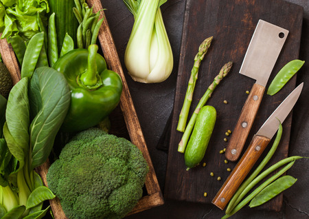 Assorted green toned raw organic vegetables in wooden box on dark stone background. Avocado, cabbage, cauliflower and cucumber with trimmed beans and chopping board with knife. Banco de Imagens