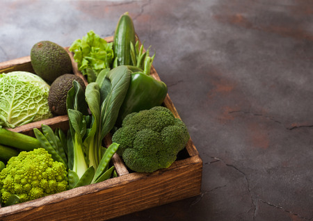 Assorted green toned raw organic vegetables in wooden box on dark stone background. Avocado, cabbage, cauliflower and cucumber with trimmed and mung beans and pepper and broccoli with sparagus tips. Banco de Imagens