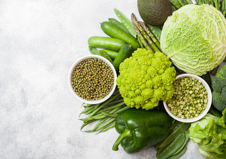 Assorted green toned raw organic vegetables on white background. Avocado, cabbage, broccoli, cauliflower and cucumber with trimmed mung beans and split peas in white bowl.
