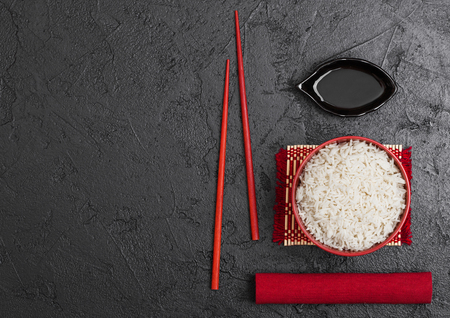 Red bowl with boiled organic basmati jasmine rice with red chopsticks and sweet soy sauce on bamboo placemat with red linen towel on black stone background.