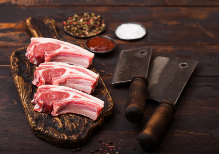 Fresh raw butchers lamb beef cutlets on chopping board with vintage meat hatchets on wooden background.Salt, pepper and oil