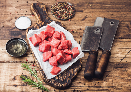 Raw lean diced casserole beef pork steak on chopping board with vintage meat hatchets on wooden background. Salt and pepper