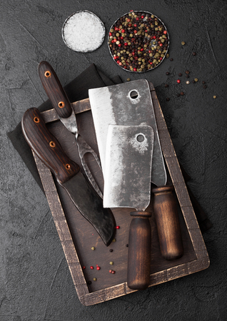 Vintage meat knife and fork and hatchet in old wooden box on black table background. Butcher utensils.