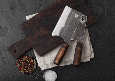 Vintage meat knife hatchet on vintage chopping board and black stone table background. Butcher utensils.