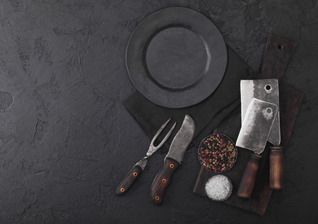 Vintage meat knife and fork and hatchets with vintage chopping board and plate on black table background. Butcher utensils.