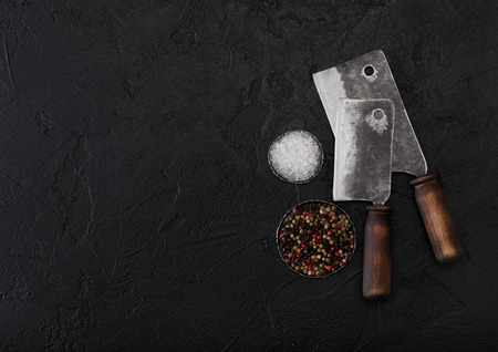 Vintage meat knife hatchets on black stone table background with salt and pepper. Butcher utensils.