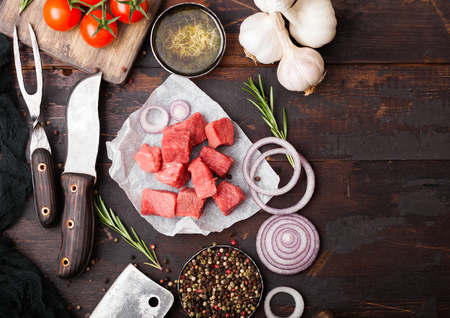 Raw lean diced casserole beef pork steak with vintage meat hatchet and knife and fork on wooden background. Salt and pepper with fresh rosemary, red onion and garlic.
