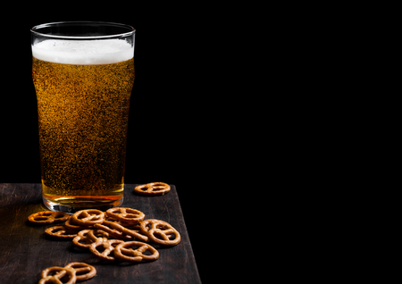 Glass of lager beer with pretzel snack on vintage wooden board on black.