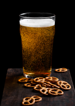 Glass of lager beer with pretzel snack on vintage wooden board on black. Imagens - 124881024