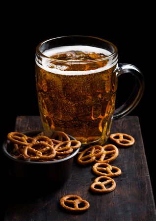 Glass of lager beer with pretzel snack on vintage wooden board on black. Imagens - 124881025