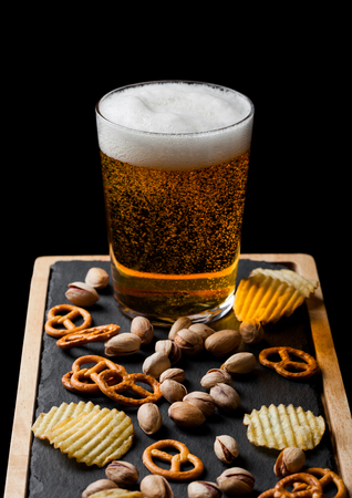 Glass of lager beer with snack on stone board on black. Pistachios and pretzel with potato crisps Imagens