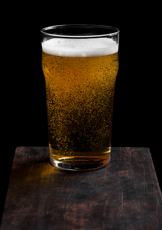 Glass of lager beer with foam and bubbles on vintage wooden board on black.