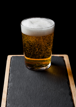 Glass of lager beer with foam and bubbles on stone board on black.