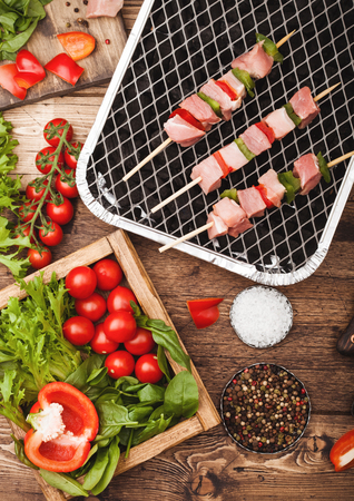 Raw pork kebab with paprika on disposable coal bbq grill with fresh vegetables on wooden background with fork and knife. Salt and pepper with lettuce and paprika.