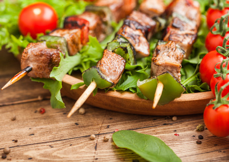 Grilled pork and chicken kebab with paprika in round wooden plate of lettuce salad, on wooden background with tomatoes and spinach. Reklamní fotografie