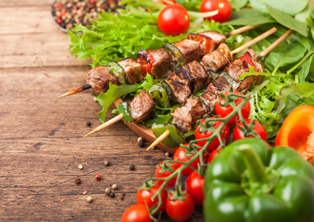 Grilled pork and chicken kebab with paprika in round wooden plate of lettuce salad, on wooden background with tomatoes and paprika.