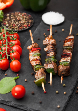Grilled pork and chicken kebab with paprika on stone chopping board with salt, pepper and tomatoes on black background. Fresh lettuce and paprika pepper.