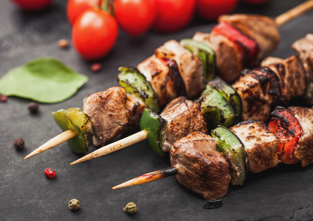 Grilled pork and chicken kebab with paprika on stone chopping board with salt, pepper and tomatoes on black. Macro Reklamní fotografie