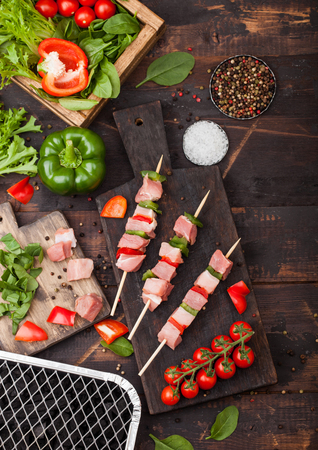 Raw pork kebab with paprika on chopping board with fresh vegetables and disposable charcoal grill on wooden background. Salt and pepper with lettuce and paprika pepper. Reklamní fotografie