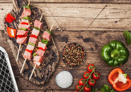 Raw pork kebab with paprika on chopping board with fresh vegetables and disposable charcoal grill on wooden background with fork and knife. Salt and pepper with lettuce and paprika.