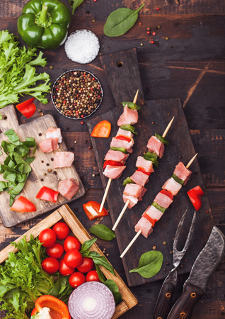 Raw pork kebab with paprika on chopping board with fresh vegetables on wooden background with fork and knife. Salt and pepper with lettuce and paprika and cherry tomatoes.