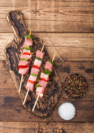 Raw pork kebab with paprika on vintage chopping board with salt and pepper on wood.