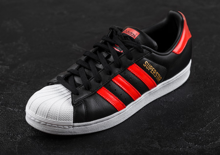 LONDON, UK - JUNE 05, 2019: Adidas Originals Superstar black shoe with red stripes on black background. Editorial