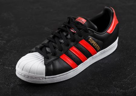 LONDON, UK - JUNE 05, 2019: Adidas Originals Superstar black shoe with red stripes on black background. Reklamní fotografie - 124998861