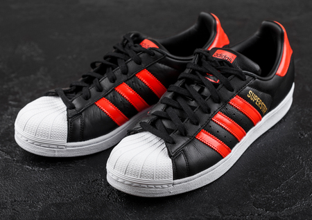LONDON, UK - JUNE 05, 2019: Adidas Originals Superstar black shoes with red stripes on black background.