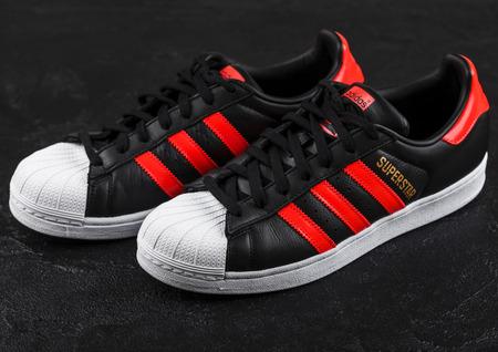 LONDON, UK - JUNE 05, 2019: Adidas Originals Superstar black shoes with red stripes on black background. Reklamní fotografie - 124998863