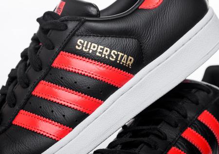 LONDON, UK - JUNE 05, 2019: Adidas Originals Superstar black shoes with red stripes on white background. Zdjęcie Seryjne - 124998864