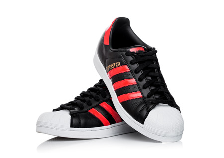 LONDON, UK - JUNE 05, 2019: Adidas Originals Superstar black shoes with red stripes on white background. 報道画像