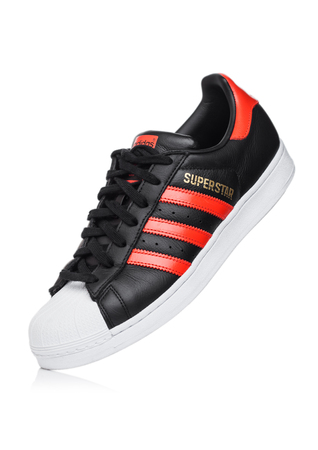 LONDON, UK - JUNE 05, 2019: Adidas Originals Superstar black shoe with red stripes on white background. Zdjęcie Seryjne - 124998867