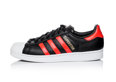 LONDON, UK - JUNE 05, 2019: Adidas Originals Superstar black shoe with red stripes on white background. Editorial